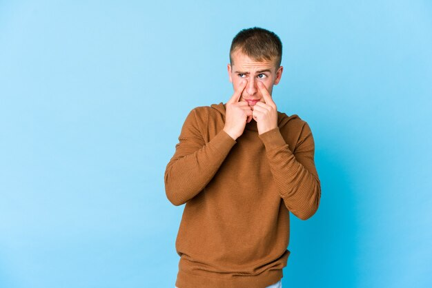 Giovane uomo caucasico bello piangere, insoddisfatto di qualcosa, agonia e concetto di confusione.