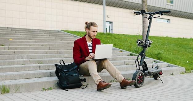 Giovane uomo caucasico bello in occhiali e giacca rossa seduto sui gradini all'aperto, lavorando su un computer portatile, digitando sulla tastiera. un ragazzo elegante lavora in strada come libero professionista. scooter elettrico. libero professionista.
