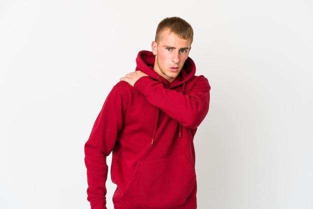Giovane uomo caucasico bello che ha un dolore alla spalla.