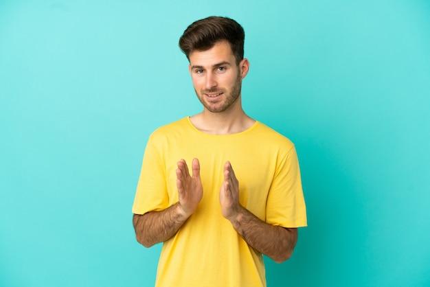 Giovane uomo caucasico bello isolato su sfondo blu che applaude dopo la presentazione in una conferenza