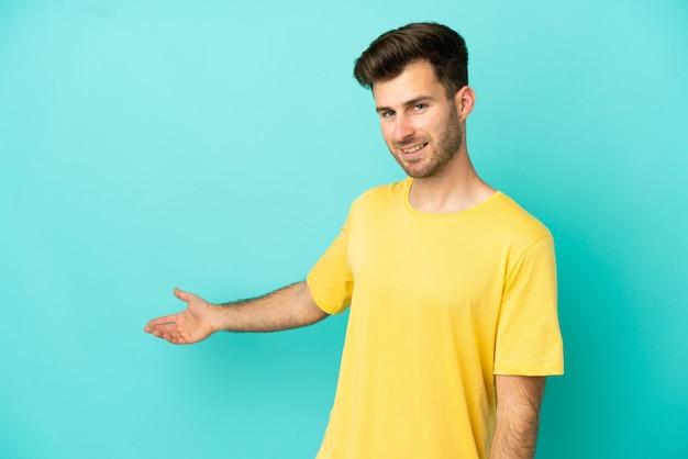 Giovane uomo caucasico bello isolato su sfondo blu che allunga le mani di lato per invitare a venire