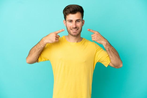 Giovane uomo caucasico bello isolato su sfondo blu che dà un gesto di pollice in alto