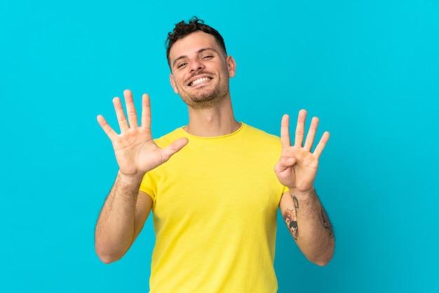 Giovane uomo caucasico bello isolato sulla parete blu che conta nove con le dita