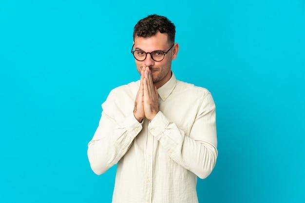 Il giovane uomo bello caucasico isolato sulla parete blu tiene insieme la palma. la persona chiede qualcosa