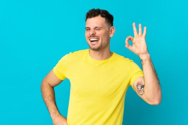 Giovane uomo caucasico bello isolato sulla parete blu che mostra segno giusto con le dita