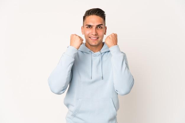 Giovane uomo caucasico bello isolato che celebra una vittoria, passione ed entusiasmo, felice espressione.