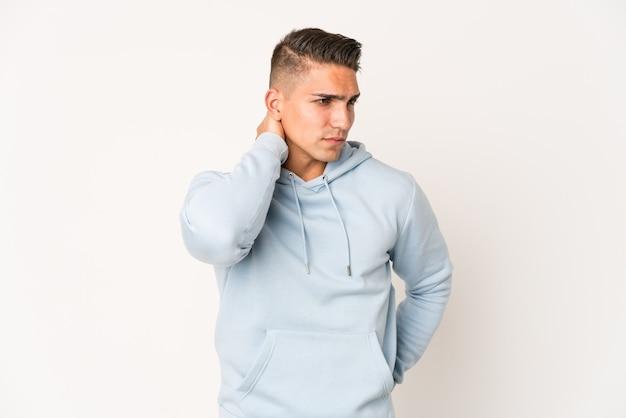 Giovane uomo caucasico bello isolato avendo un dolore al collo a causa dello stress, massaggiandolo e toccandolo con la mano.