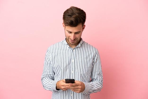 Giovane uomo caucasico bello isolato su sfondo rosa che invia un messaggio con il cellulare