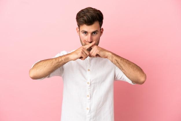 Giovane uomo caucasico bello isolato su sfondo rosa che mostra un segno di gesto di silenzio