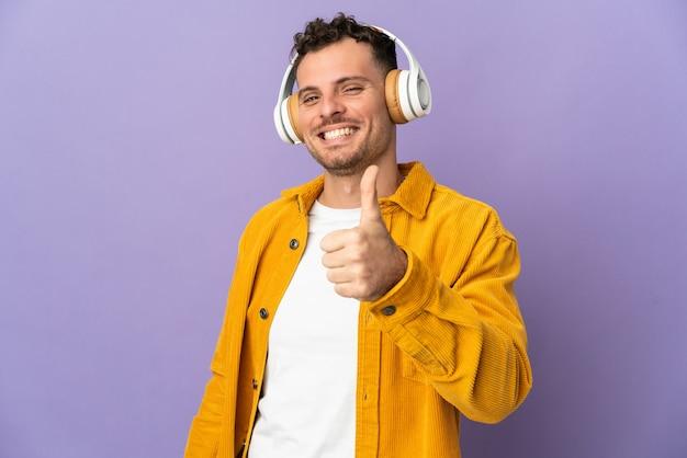 Giovane uomo caucasico bello isolato sulla musica d'ascolto viola e con il pollice in su