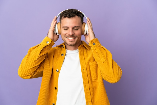 Giovane uomo caucasico bello isolato sulla musica d'ascolto viola