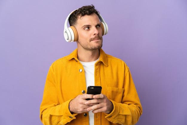 Giovane uomo caucasico bello isolato sulla musica d'ascolto della parete viola con un cellulare e un pensiero