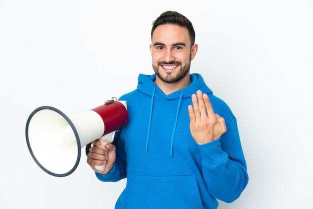 Giovane uomo caucasico bello isolato su sfondo bianco che tiene in mano un megafono e invita a venire con la mano