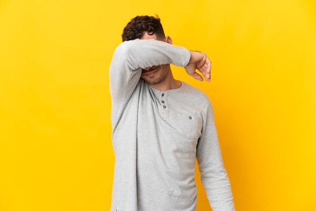 Giovane uomo caucasico bello isolato sulla parete gialla che copre gli occhi con le mani