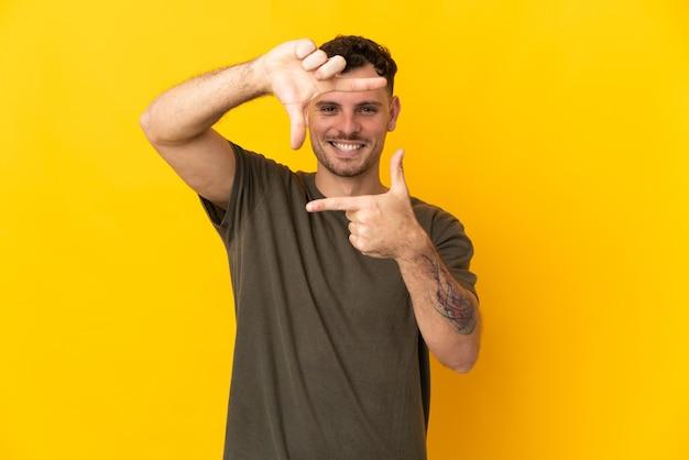 Giovane uomo caucasico bello isolato sulla parete gialla che mette a fuoco il fronte. simbolo di inquadratura