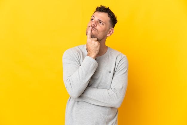Giovane uomo caucasico bello isolato sulla parete gialla che ha dubbi mentre osserva in su