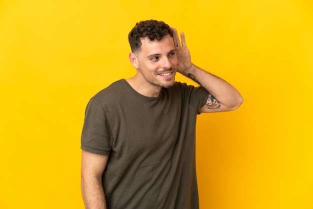 Giovane uomo caucasico bello isolato sulla parete gialla che ascolta qualcosa mettendo la mano sull'orecchio