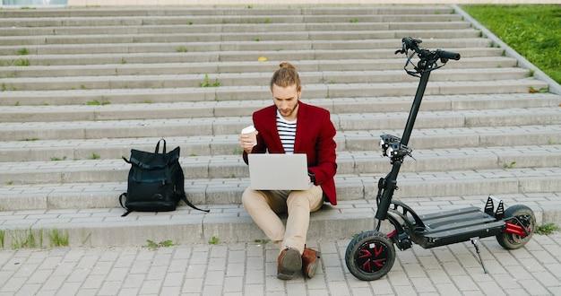 Giovane uomo caucasico bello in giacca rossa seduto sui gradini all'aperto, lavorando su un computer portatile, sorseggiando un drink. ragazzo alla moda che beve caffè. libero professionista impegnato. scooter elettrico. libero professionista.