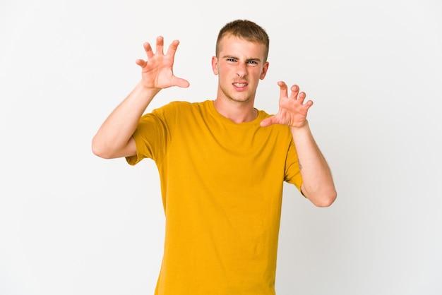 Giovane uomo caucasico bello che mostra gli artigli che imitano un gatto, gesto aggressivo.
