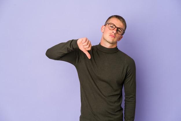 Giovane uomo caucasico bello che mostra un gesto di avversione, pollice in giù. concetto di disaccordo.