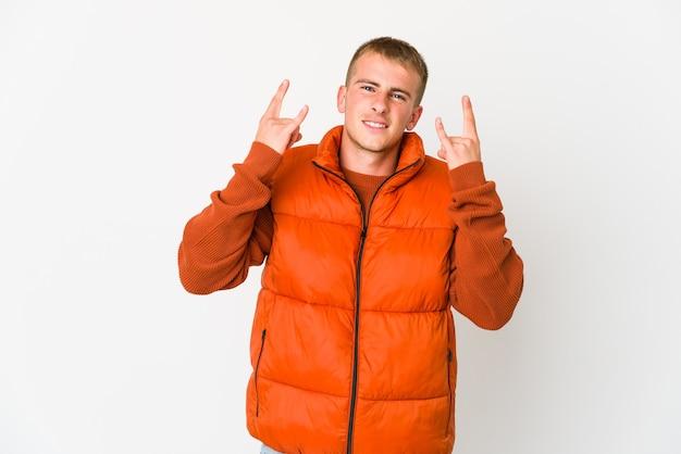 Giovane uomo caucasico bello che mostra un gesto di corna come un concetto di rivoluzione.