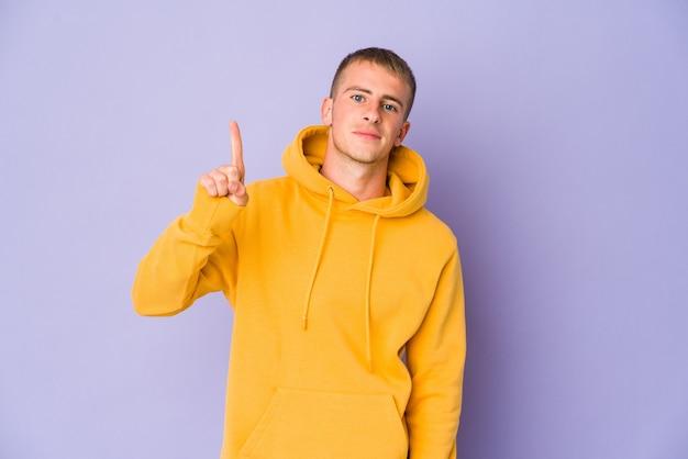 Giovane uomo caucasico bello che mostra il numero uno con il dito.