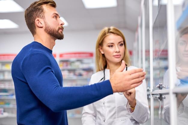 Giovane farmacista femminile utile caucasico che si occupa di un cliente maschio