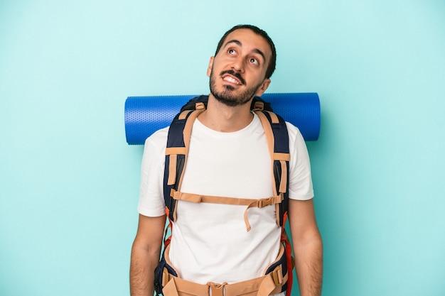 Giovane uomo caucasico escursionista isolato su sfondo blu che sogna di raggiungere obiettivi e scopi