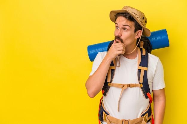 Giovane uomo caucasico escursionista isolato su sfondo giallo guardando lateralmente con espressione dubbiosa e scettica.