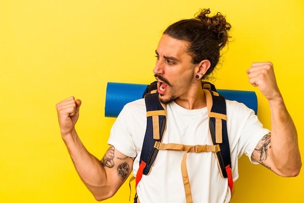 Giovane uomo caucasico della viandante con capelli lunghi isolato su fondo giallo che alza il pugno dopo una vittoria, concetto del vincitore.