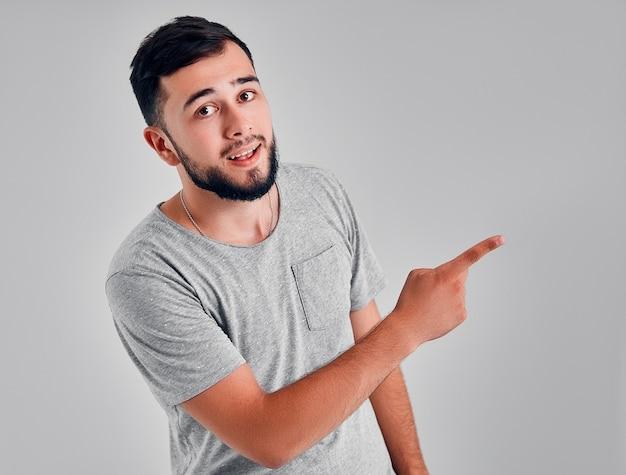 Giovani caucasici hipster uomo che indossa una maglietta grigia su sfondo isolato allegro con un sorriso del viso rivolto con la mano e il dito fino al lato con espressione felice e naturale sul viso