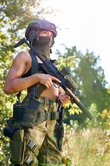 Giovane donna caucasica cacciatore in cima con una pistola durante la caccia alla ricerca di uccelli selvatici