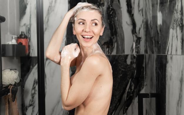 La giovane signora caucasica prende una doccia. capelli in testa con la schiuma dello shampoo, ho visto qualcuno e ho sorriso allegramente. vista laterale, banner
