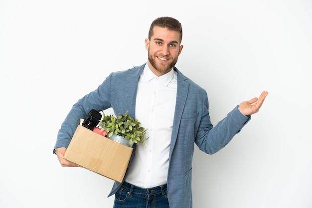 Giovane caucasico che fa una mossa mentre prende in mano una scatola piena di cose isolate su bianco che estende le mani di lato per invitare a venire