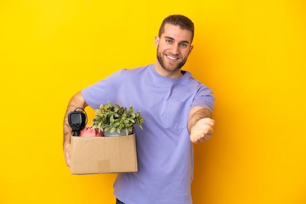 Giovane caucasico che fa una mossa mentre prende in mano una scatola piena di cose isolate sul muro giallo che stringe la mano per chiudere un buon affare