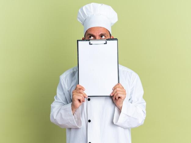 Giovane cuoco maschio caucasico in uniforme da chef e cappuccio che tiene appunti guardando in alto da dietro isolato su parete verde oliva