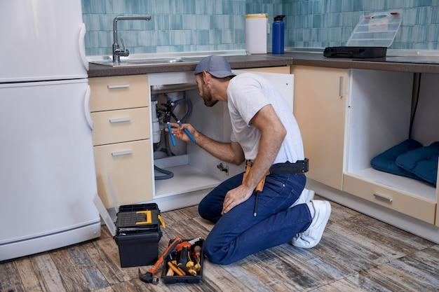 Giovane lavoratore maschio caucasico che fissa i tubi sotto il lavello della cucina