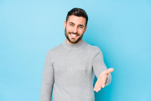 Giovane uomo caucasico contro una mano di allungamento isolata blu nel gesto di saluto.