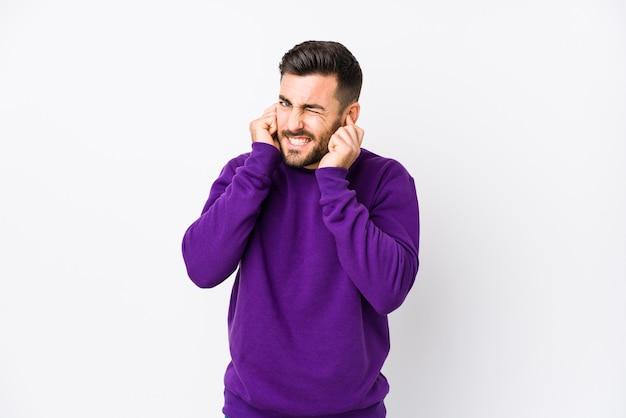 Giovane uomo caucasico contro uno sfondo bianco isolato che copre le orecchie con le mani.