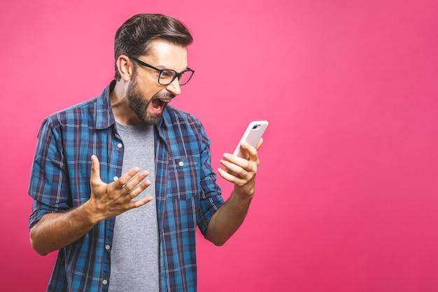 Giovane uomo caucasico arrabbiato, frustrato e furioso con il suo telefono, arrabbiato con il servizio clienti