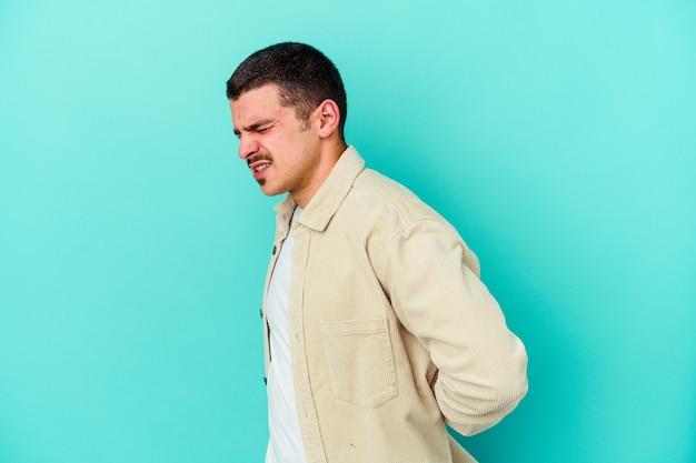 Giovane uomo caucasico su blu che soffre di mal di schiena.
