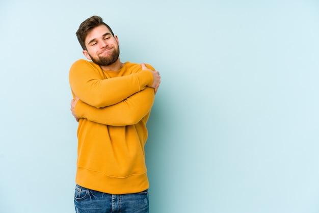 Giovane uomo caucasico sugli abbracci blu della parete, sorridente spensierato e felice.