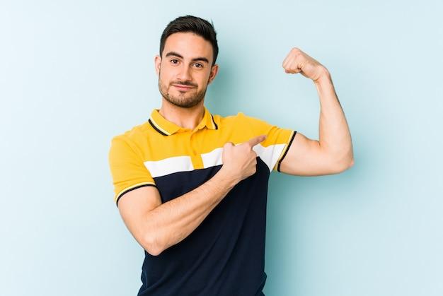 Giovane uomo caucasico sulla parete blu che mostra il gesto di forza con le braccia