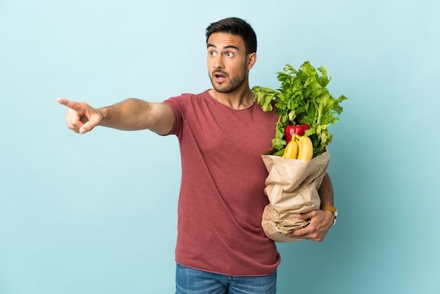 Giovane uomo caucasico l'acquisto di alcune verdure isolate su sfondo blu che punta lontano