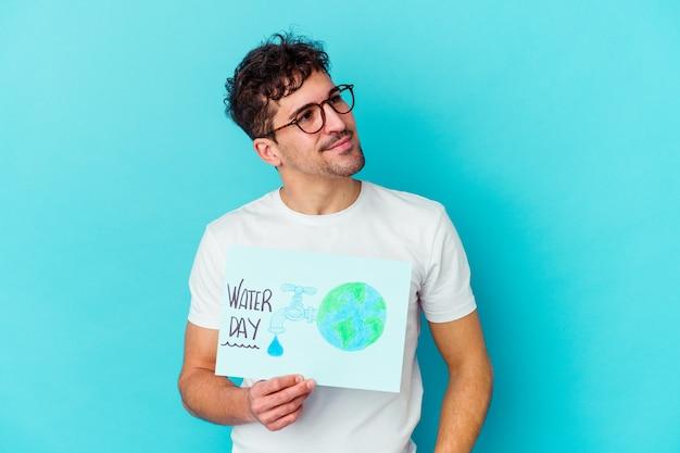 Giovane uomo caucasico che celebra la giornata mondiale dell'acqua isolato sognando di raggiungere obiettivi e scopi