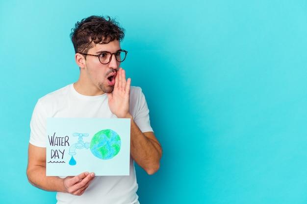 Il giovane uomo caucasico che celebra la giornata mondiale dell'acqua isolata sta dicendo una notizia segreta di frenata calda e sta guardando da parte