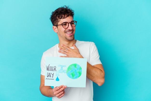 Il giovane uomo caucasico che celebra la giornata mondiale dell'acqua isolata ride ad alta voce mantenendo la mano sul petto.