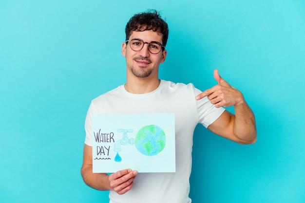 Giovane uomo caucasico che celebra la persona isolata giornata mondiale dell'acqua che punta a mano uno spazio della copia della camicia, orgoglioso e fiducioso