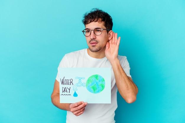 Giovane uomo caucasico che celebra la giornata mondiale dell'acqua isolato cercando di ascoltare un pettegolezzo.