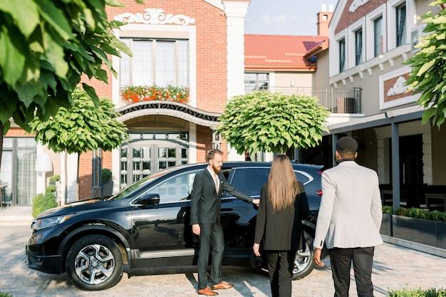 Giovane autista o partner caucasico dell'uomo nella porta di automobile di apertura del vestito all'uomo d'affari africano e donna di affari caucasica, vista posteriore